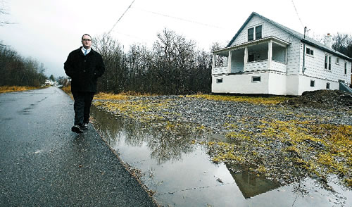 Justin Taylor walks along the 200 block of South Park St. in Carbondale where water runoff from mines has been a problem and is sladed for corrective measures. (Michael J. Mullen)