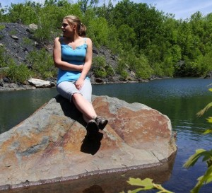 Cait Dickson, EPCAMR Watershed Outreach Intern, sitting on a rock in a flooded stripping pit in the Jim Thorpe Area.